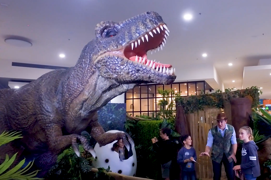 Animatronic T-rex, costumed tour guide and children enjoying the Dino World Kid's school holiday activity at Stockland Riverton shopping centre