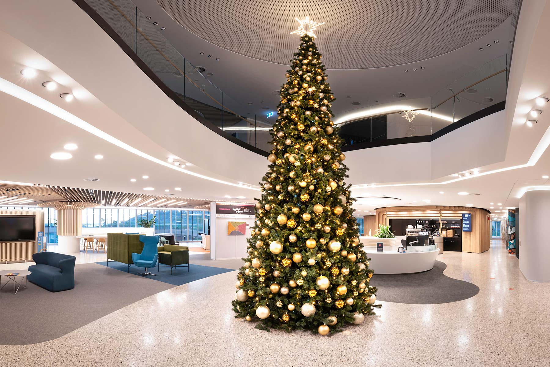 Six and a half metre tall Christmas tree decorated in rich golds in Woodside Energy's corporate foyer, Perth