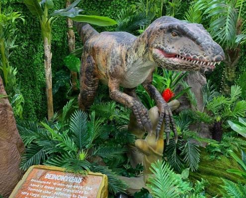 Dino World kid's school holiday activity features an animatronic deinonychus in a prehistoric jungle setting, seen here at Stockland Riverton Shopping Centre