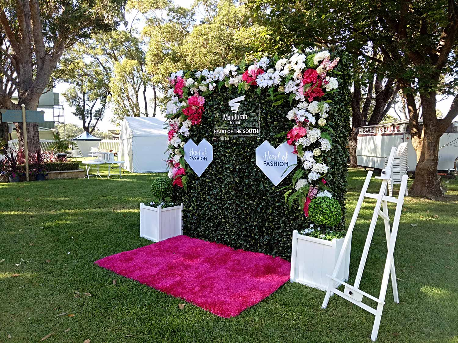 Selfie wall composed of red carpet, hedge panel and floral embellishments for fashion promotion at Mandurah Forum shopping centre